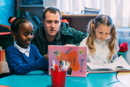 Two Children Reading With Teacher