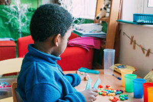 Boy playing with colourful pieces
